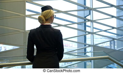 Stewardess with glasses on her face look out the window at the city.