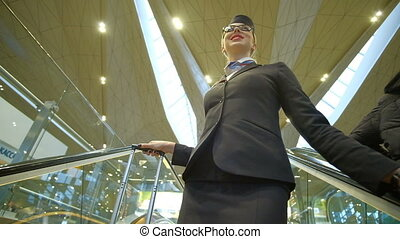 Stewardess with glasses on his face coming down the escalator.