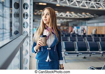 Stewardess with hand luggage and coffee in airport