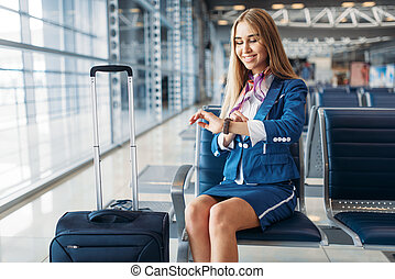 Stewardess with suitcase sitting in waiting area