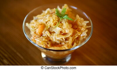 stewed cabbage with carrots in a glass bowl on a wooden...