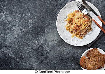 Stewed cabbage with meat on a plate. Dark concrete background. Copy space