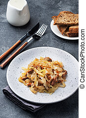 Stewed cabbage with meat on a plate. Dark concrete background.