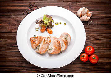 Stewed chicken fillet with vegetables and seasoning on a wooden background