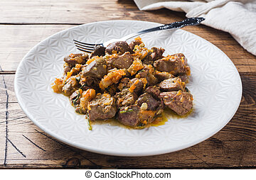 Stewed chicken liver with vegetables on a plate. Wooden background.