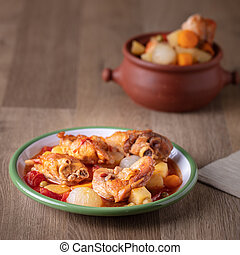 Stewed Chicken with vegetables on brown background