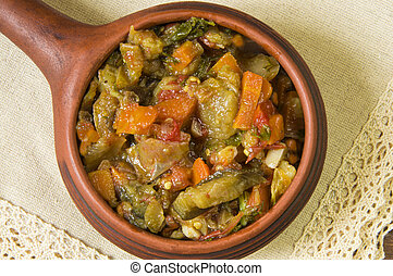 Stewed vegetables in a ceramic frying pan on a white napkin