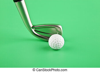 Stick and golf ball on a green background