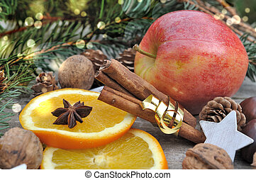 stick of cinnamon in golden ribbon with fruits