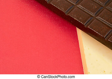 Stick of white and dark chocolate on a red background