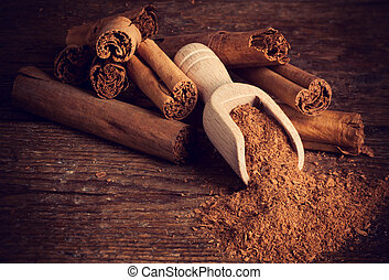 Sticks and ground ceylon cinnamon with wood spoon on wooden...