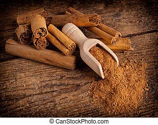 Sticks and ground ceylon cinnamon with wood spoon on wooden table