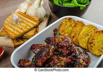 Sticky chicken wings with garlic bread panini, rustic spicy potatoes, fresh spinach leaves