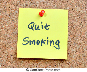 Quit smoking - sticky note on an office cork bulletin board ...
