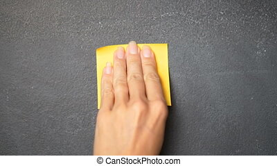 Sticky note on the blackboard - Closeup woman's hand...