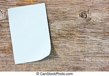 Sticky note on the wooden background