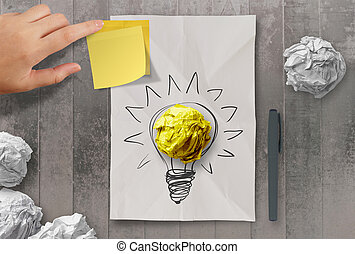 sticky note with another idea light bulb on crumpled paper ...