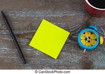 sticky note with empty space for a text and Cup of coffee on  wooden background.  New Year resolutions concept