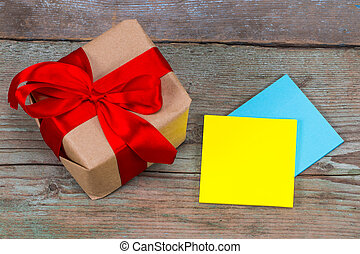 sticky note with empty space for a text and gift with red ribbon on wooden background