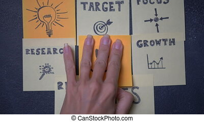 Sticky notes on the blackboard - Closeup woman's hand...
