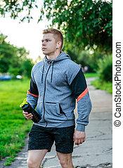 stile di vita, primo piano, suo, headphones., sano, bodybuilder., atleta, prese, maschio, aria., mano, acqua, protein., musica, bottiglia, fuori, lui, aperto, ascolta