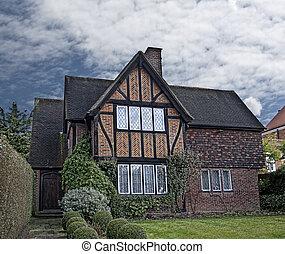 Stile tudor casa drammaticamente roofline mattone for Piani di casa di log in stile ranch