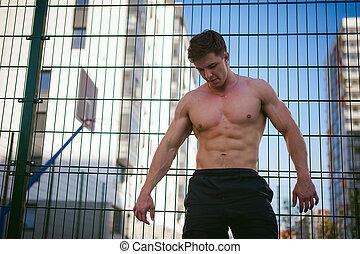 stilig, sexig, manlig, bodybuilder, atlet, man, med, naken, torso, ge sig sken, visande, a, mäktig, muskulös, kropp, stående, nära, a, grön, galler, staket, sporter gärde, in, courtyard., frisk livsstil, concept.