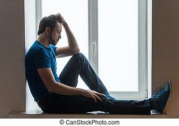 stilig, ung man, sittande, på, windowsill., grabb, hållande huvud, och, tröttsam, blå skjorta, och, jeans