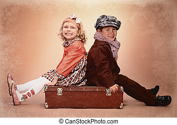 still ahead - Cute little boy is sitting on the old suitcase...