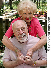 Still In Love - A happy senior couple embracing outdoors. ...
