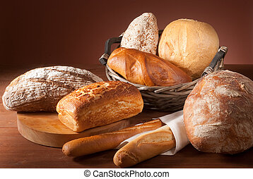 still-life assortment of baked bread over brown background
