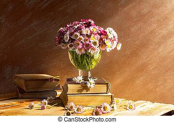 Still life bouquet daisies books
