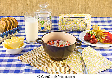 Still life breakfast of oat porridge with strawberries on a checkered tablecloth