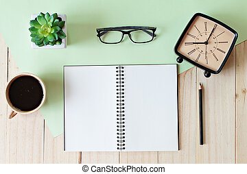 Top view of working desk with blank notebook with pencil, coffee cup, eyeglasses, retro alarm clock and plant on wooden background