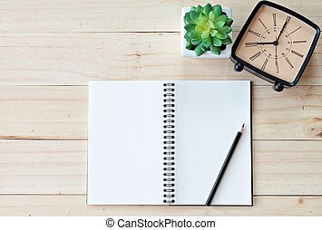 Top view of working desk with blank notebook with pencil, retro alarm clock and plant on wooden background