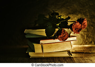 still life flowers on a books old in the dark - Red rose flowe tone vintage style