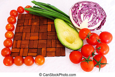 Still life frame from wooden cutting board, cherry tomatoes and greens, avocado and red cabbage