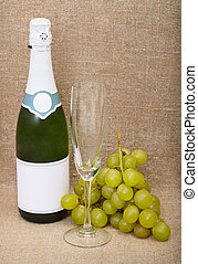 Still-life from a bottle of a sparkling wine, empty glass and grapes against a canvas