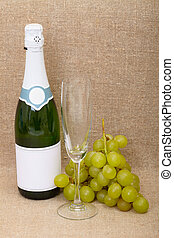 Still-life from a bottle of sparkling wine, a glass and grapes cluster