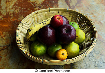 Still life fruts with apple banana and orange in basket weave on wooden table