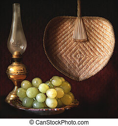 Still life, grapes, oil lamp and fan