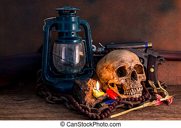 Still life, human skulls with shot gun, and lamp on wooden table