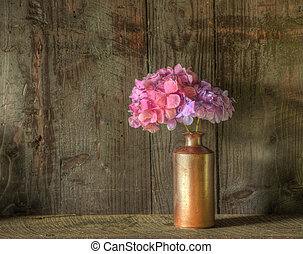 Still life image of dried flowers in rustic vase against ...