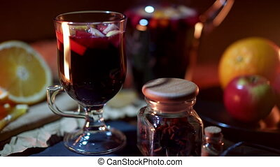 Still life - mulled wine, hot red wine with spices in glass among fruits. Scented cozy Christmas celebration, fragrant punch concept. High quality 4k footage