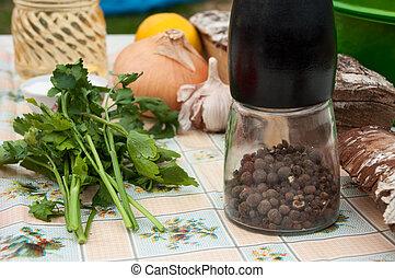 Still life of black pepper, parsley, onion, garlic and birch firewood on background