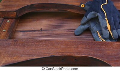 Still life of carpentry. Wooden table, gloves and...