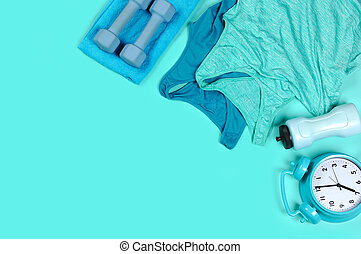still life of dumbbells, water flash, towel, clock and jogging tops in blue color