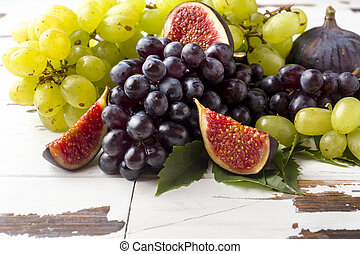 Still life of fresh autumn fruit. Grapes black and green, figs and leaves on a wooden table with copy space.
