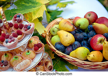Still life of fresh fruit in the basket and cake on a plate with autumn leaves