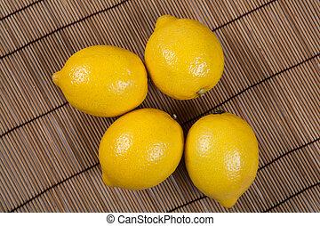 Still life of fresh lemons on a bamboo napkin